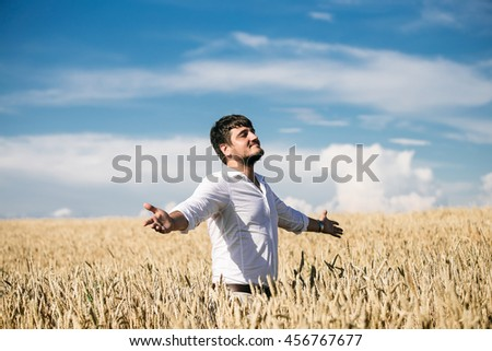 handsome businessman in white shirt standing in field of wheat. Raised arms. outdoor shot