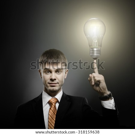 handsome businessman index finger point upwards with light bulb, on dark background - stock photo