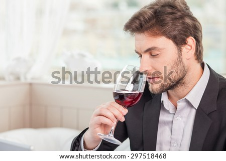 Handsome businessman is drinking red wine with enjoyment. He is sitting and holding wineglass with pleasure. Copy space in left side - stock photo