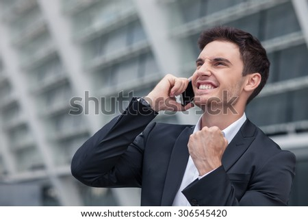 Handsome businessman is standing and talking on the phone with his client. The deal was done successfully. The worker is smiling and raising his fist up happily - stock photo