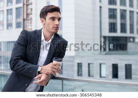 Handsome businessman is standing near his office and leaning on the border. He is drinking coffee and relaxing. The man is looking aside dreamingly. Copy space in right side - stock photo