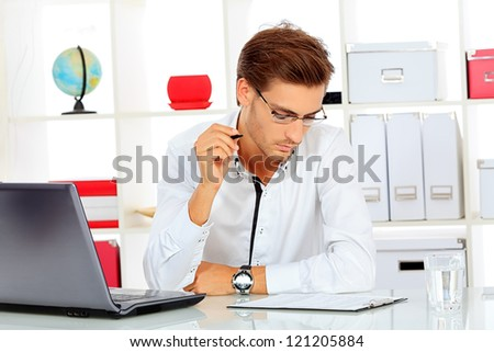 Handsome businessman is working on a laptop at the office. - stock photo