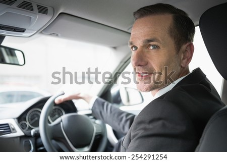 Handsome businessman looking at camera in his car - stock photo