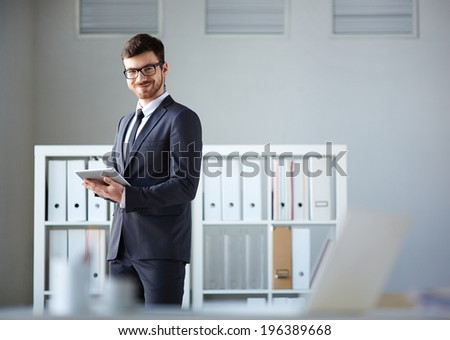 Handsome businessman looking at camera while networking in office - stock photo