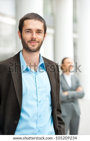 Handsome businessman looking at camera with his partner behind - stock photo