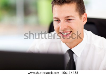 handsome businessman looking at computer screen at workplace