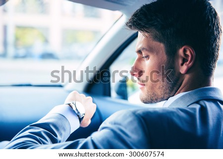 Handsome businessman looking on wrist watch in car - stock photo