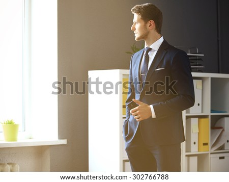 Handsome businessman looking through window - stock photo