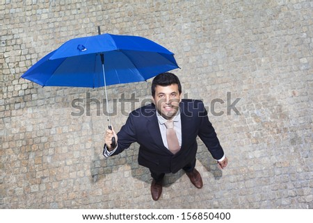 Handsome businessman looking to the sky and checking if it's raining - stock photo
