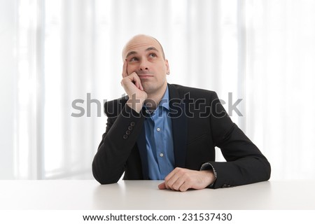 handsome businessman looking up and thinking in the office - stock photo
