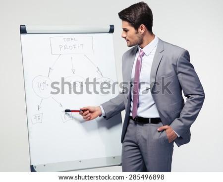 Handsome businessman making presentation on flipchart over gray background - stock photo