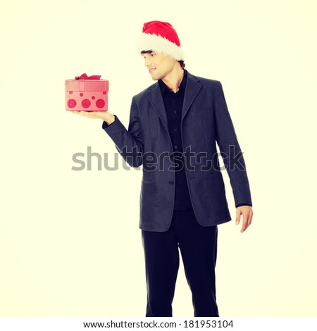 Handsome businessman offering a christmass gift. - stock photo