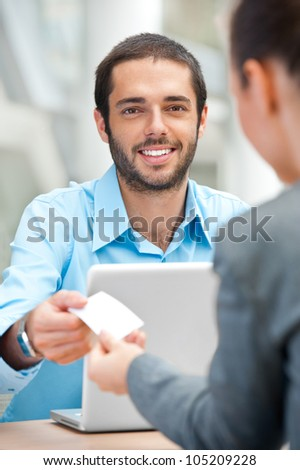 Handsome businessman offering his visiting card to partner - stock photo