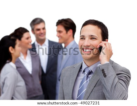 Handsome businessman on phone standing apart from his team against a white background