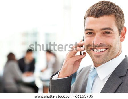 Handsome businessman on the phone in the foreground while his team is working in the office - stock photo