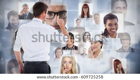 Handsome businessman pointing at a copy space against grey background