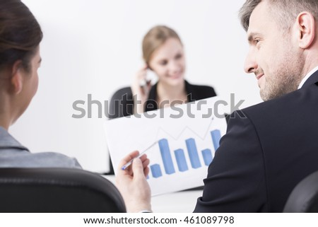 Handsome businessman pointing at graph during business meeting