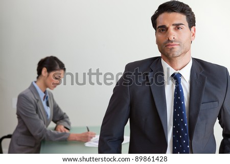 Handsome businessman posing while his colleague is working in an office - stock photo