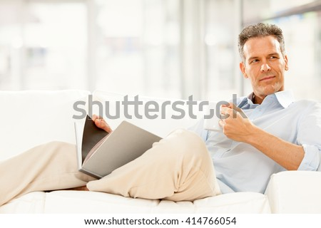 handsome businessman read and drink cup of tea on the couch at home