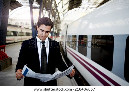 Handsome businessman reading newspaper standing in platform of big railway station, successful rich man in black suit reading news on the way to work in train station, business and finance