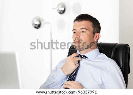 handsome businessman readjusting his tie in office - stock photo