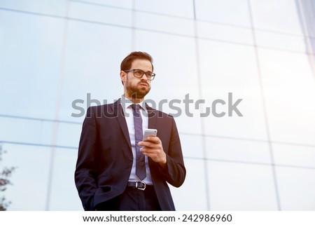 Handsome businessman receiving shocking news as he reads a text message on mobile phone - stock photo