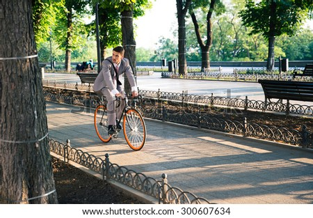 Handsome businessman riding bicycle to work in park - stock photo