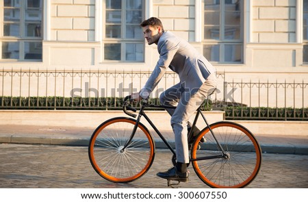 Handsome businessman riding bicycle to work on urban street in morning - stock photo