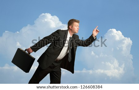 Handsome businessman running with briefcase outside - stock photo