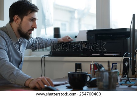 Handsome businessman scanning and printing document in office - stock photo