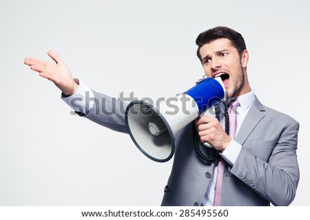 Handsome businessman screaming in loudspeaker over gray background - stock photo