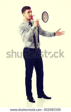 Handsome businessman shouting through megaphone. - stock photo