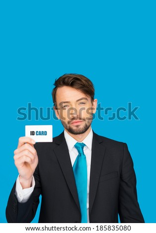 handsome businessman showing blank business card on blue
