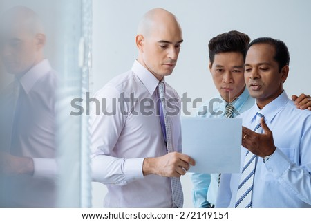 Handsome businessman showing document to his colleagues - stock photo