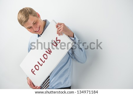 """Handsome businessman showing """"follow us"""" text on a billboard - stock photo"""