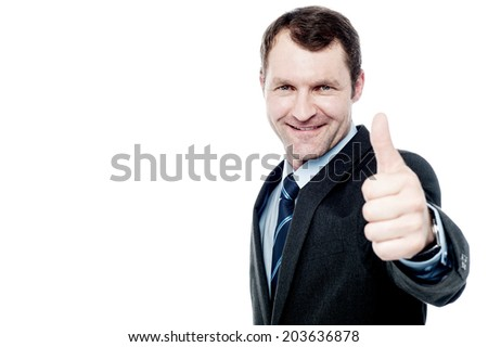 Handsome businessman showing thumbs up gesture - stock photo