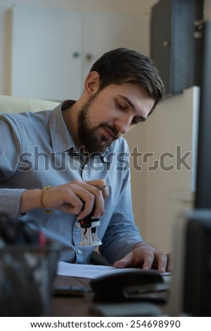 Handsome businessman signing contract in office - stock photo