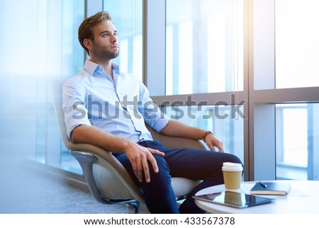 Handsome businessman sitting at a coffee table in a bright office space with large windows, thinking about the future while looking optimistically out of the window - stock photo