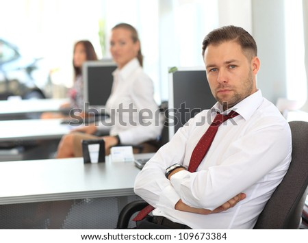 Handsome businessman sitting at desk using computer with colleagues in back - stock photo