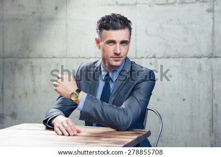 Handsome businessman sitting at the table and looking at camera over concrete wall - stock photo