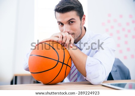Handsome businessman sitting at the table with ball in office and looking at camera
