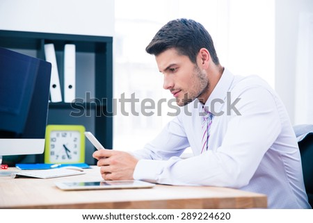 Handsome businessman sitting at the table with smartphone in office