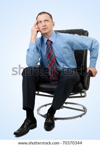 Handsome businessman sitting in a armchair and  thinking, over blue background - stock photo