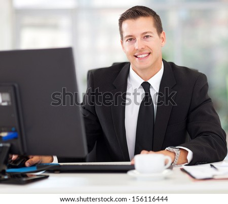 handsome businessman sitting in office working on computer - stock photo