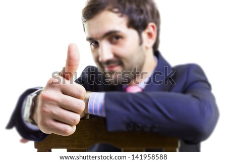 Handsome businessman sitting on a chair with thumb up, isolated on white - stock photo
