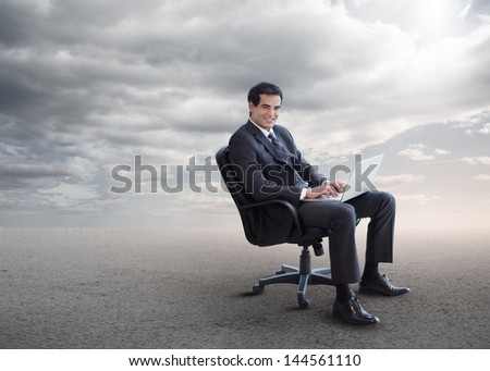 Handsome businessman sitting on a swivel chair and using his laptop
