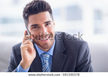 Handsome businessman sitting on sofa making a call smiling at camera in the office - stock photo
