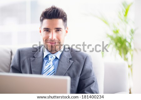 Handsome businessman sitting on sofa using his laptop in the office - stock photo