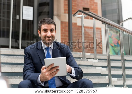 Handsome businessman sitting on steps with tablet pc