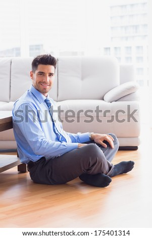Handsome businessman sitting on the floor in the office - stock photo